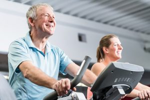 senior man and young woman spinning in fitness bike at the gym